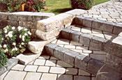 Kann Via Vecia ist ein lebendiger Pflasterbelag, der spannende Muster ermöglicht. Dazu passt die Vermont-Bruchsteinmauer mit ihrem ursprünglichen Erscheinungsbild. – Foto: Kann GmbH Baustoffwerke